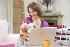 Mother and baby in home office royalty free stock photography