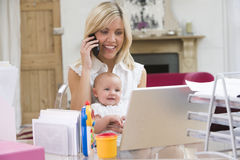 Mother and baby in home office and telephone. Mother and baby in home office with laptop and telephone