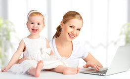 Mother and baby at home using laptop computer. Happy family mother and baby at home using laptop computer Royalty Free Stock Photography