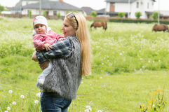 Mother with a baby on a horse farm Royalty Free Stock Photo