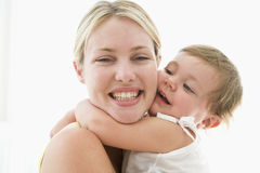 Mother and baby indoors hugging royalty free stock photography