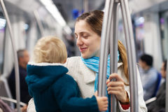 Mother with baby inside metro train. Photo of young mother with baby inside metro train royalty free stock images