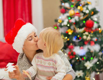 Mother and baby kissing near Christmas tree Royalty Free Stock Photos