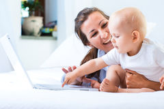 Mother and baby with laptop. Woman with baby and laptop in bed Stock Photography