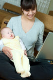 Mother, baby and laptop Stock Image