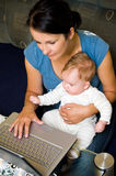 Mother, baby and laptop. Mother holding her baby daughter on her laps, using laptop computer at home Stock Photo