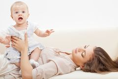 Mother and baby laying on sofa Stock Photography