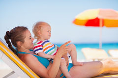 Mother with baby laying on sunbed. And pointing on copy space Royalty Free Stock Image