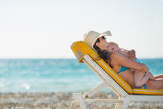 Mother with baby laying on sunbed on beach. Mother with baby girl laying on sunbed on beach Stock Photography