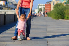 Mother and baby learning to walk in city park Royalty Free Stock Photo