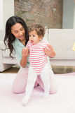 Mother with baby learning to walk Stock Images
