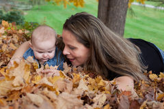 Mother and baby among leaves Royalty Free Stock Images