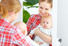 Mother and baby look in the mirror  at home Royalty Free Stock Images