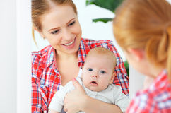 Mother and baby look in the mirror  at home Royalty Free Stock Image