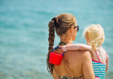 Mother and baby looking on sea. Rear view Stock Photography