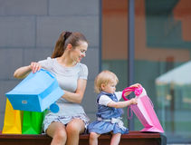 Mother and baby looking into shopping bag Royalty Free Stock Photo