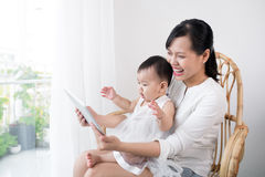 Mother and baby are looking to play and read tablet computer at Royalty Free Stock Images