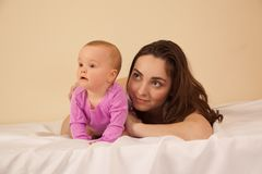 Mother with baby lying on bed Royalty Free Stock Photos