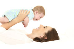 Mother and baby lying on bed Stock Photo