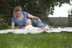 Mother And Baby Lying On Lawn Stock Photos