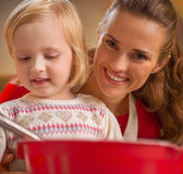 Mother and baby making christmas cookies in kitchen Royalty Free Stock Image