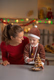Mother and baby making christmas tree from cookies Royalty Free Stock Photo