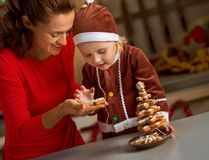 Mother and baby making christmas tree from cookies Royalty Free Stock Images