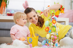 Mother and baby making Easter decoration. On sofa
