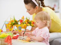 Mother and baby making Easter decorations Stock Image