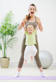 Mother and baby making gymnastics. At gym Stock Photos