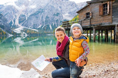 Mother and baby with map on lake braies in italy Stock Photos