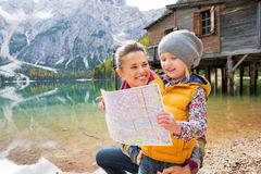 Mother and baby with map on lake braies in italy Stock Images