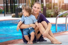 Mother with baby near the pool. Beautiful mother with cute little son sitting near the pool on the beach resort, having fun together and enjoying bright sunny royalty free stock photography