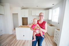 Mother and baby in new home construction. Kitchen remodel Royalty Free Stock Photo