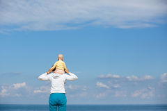 Mother and baby observing the cloudscape and sea Stock Photos