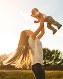 Mother with baby outdoors. Beautiful mother and her son are having fun outdoors in sunshine Royalty Free Stock Photo