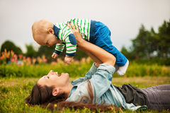Mother with baby outdoors. Beautiful young mother and her son are having fun outdoors in sunshine Stock Images