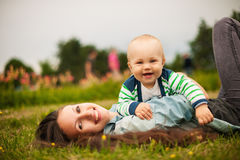 Mother with baby outdoors. Beautiful young mother and her son are having fun outdoors in sunshine Stock Photos