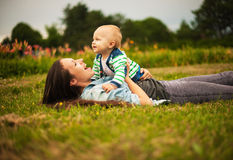 Mother with baby outdoors. Beautiful young mother and her son are having fun outdoors in sunshine Stock Photography