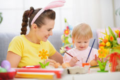 Mother and baby painting on Easter eggs Royalty Free Stock Image