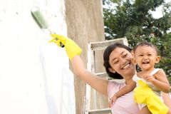Mother and baby painting together. Portrait of cheerful asian family: a mother spare her time to babysitting her 1 year old baby girl during painting work on the Royalty Free Stock Photo