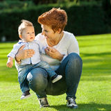 Mother and baby play on the grass Stock Photography