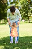 Mother and baby in park making first steps. Happy mother and baby child in park making first steps .  Walking and hugging Royalty Free Stock Image