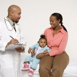 Mother and baby with pediatrician. African-American mother and baby girl with male pediatrician Stock Images
