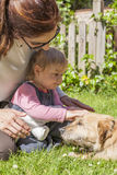 Mother and baby petting dog Royalty Free Stock Photography