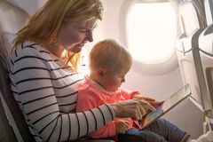 Mother and baby on plane. Playing tablet royalty free stock photo