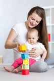 Mother and baby play with building blocks toy in nursery. Mother and baby playing with building blocks toy in nursery royalty free stock photos