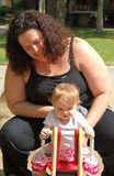 Mother and baby play on tetter totter at park Stock Images