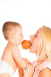 Mother and baby playing. With an apple Royalty Free Stock Photos