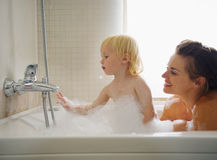 Mother and baby playing in bathtub Stock Image